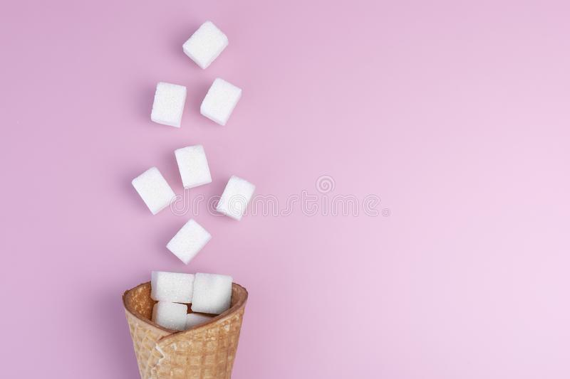 Ice cream cone with sugar cubes on bright pink background. Minimal food concept. Copy space. royalty free stock photography