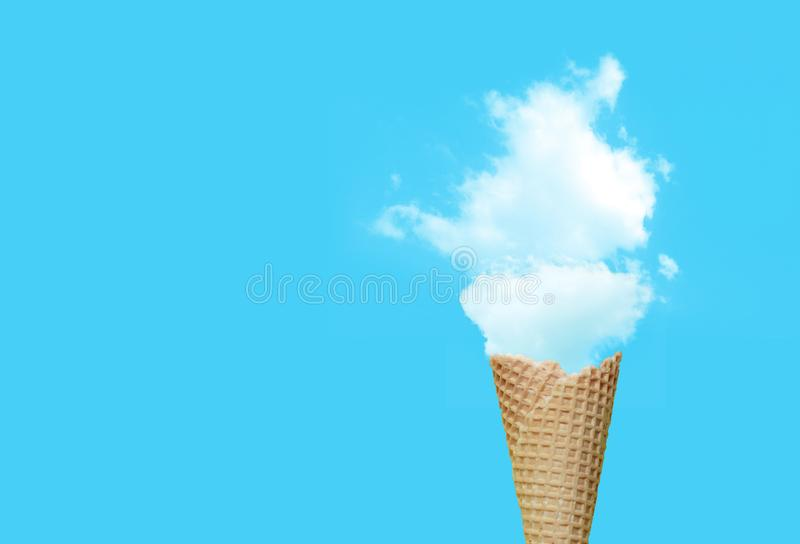 Ice cream cone with white cloud in blue background. stock photo