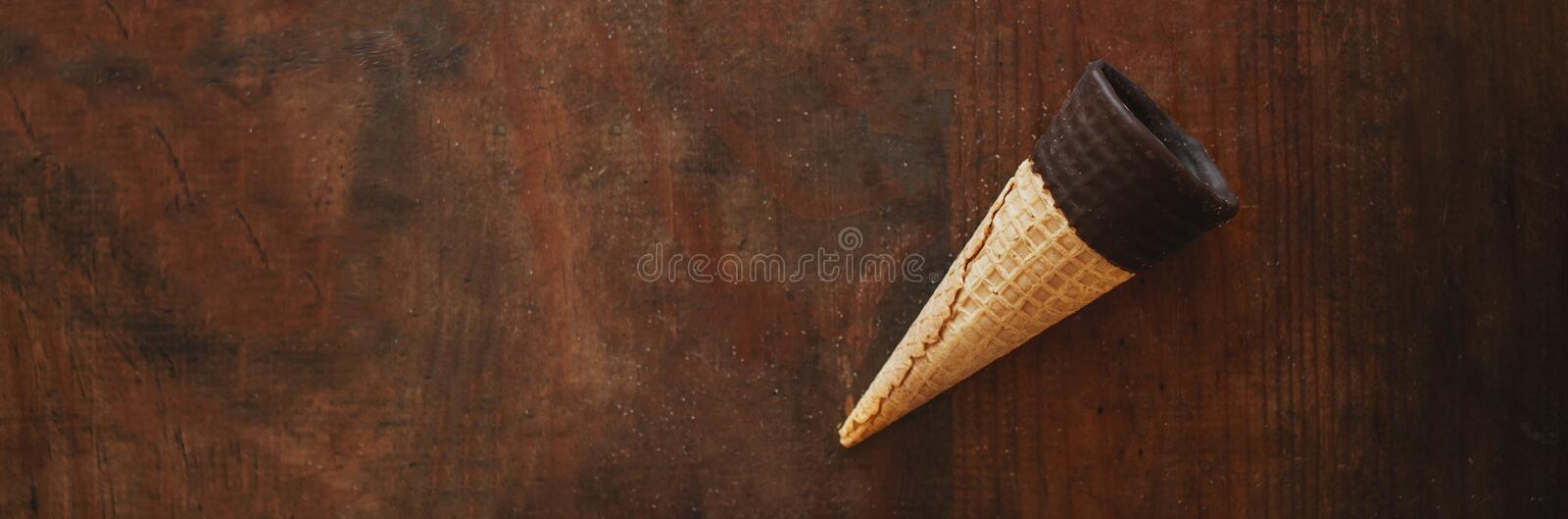 Ice cream cones. Sweet Ice-cream cones with chocolate on wooden background, flat lay. Summer concept. Top view royalty free stock photography