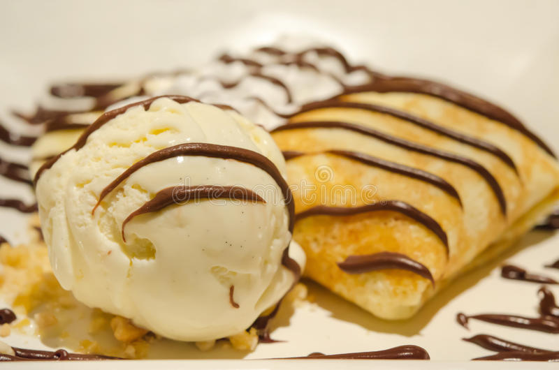 Ice cream and crepes. Close up vanilla ice cream and crepes with banana , chocolate sauce served with whipping cream stock images