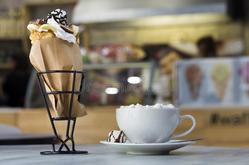 Ice cream dessert in wafer cup with chocolate cookies and and mug of coffee with marshmallows on porcelain plate on blurred stock image