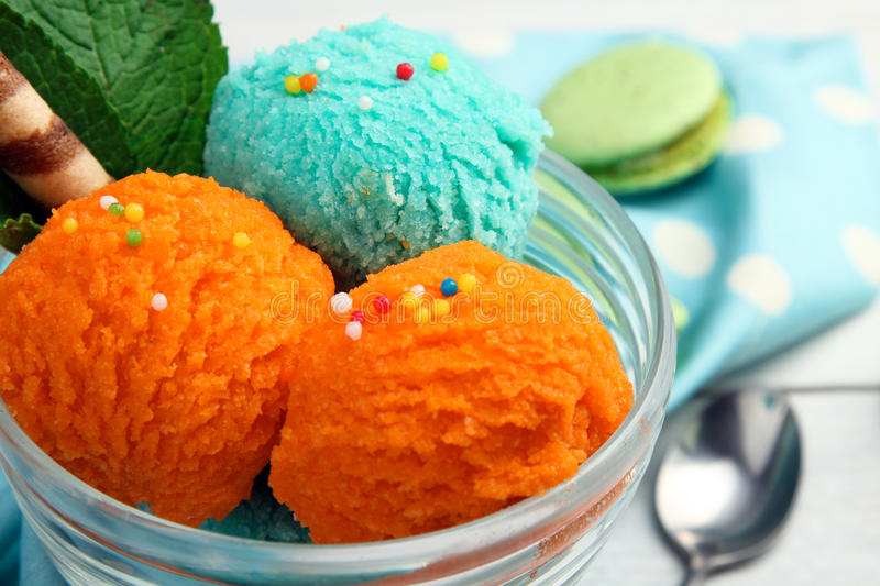Ice cream. With different flavors and mint in bowl on napkin on wooden background near to the macaroons stock images