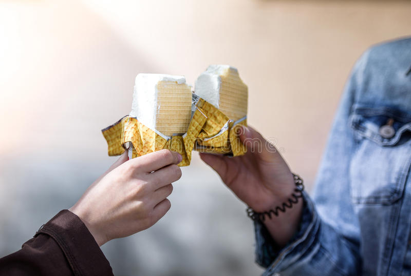 Ice cream in the hands of two girls. Close-up royalty free stock photography