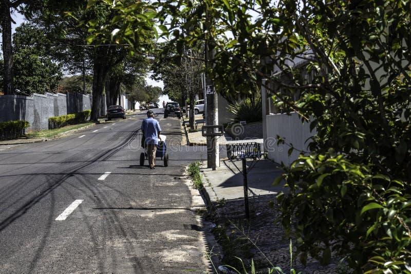 Ice cream hawker walks down a street of Marilia city. Marilia, Sao Paulo, Brazil, September 09, 2019: Ice cream hawker walks down a street of Marilia city royalty free stock image