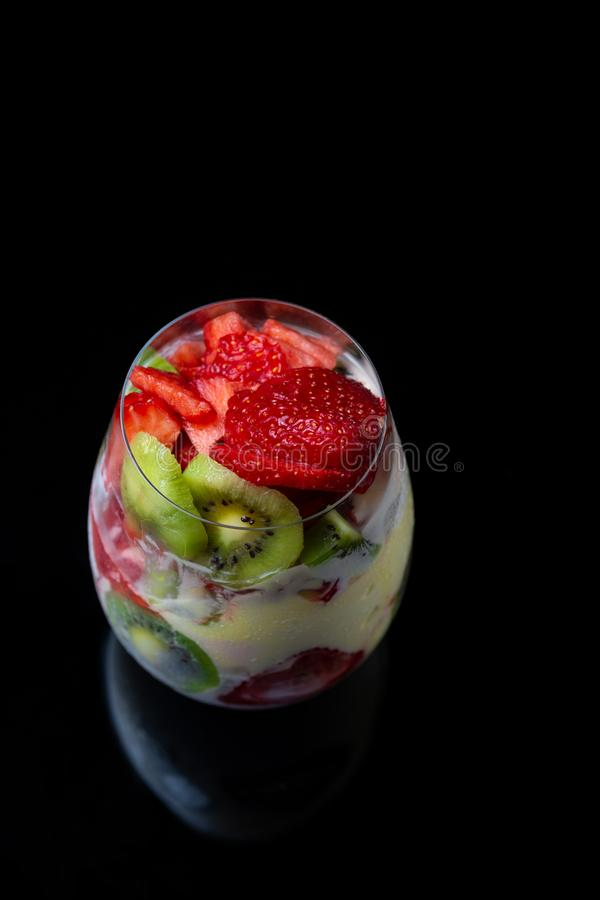 Ice cream with kiwi and strawberries in a beautiful glass cup on a black background royalty free stock photo