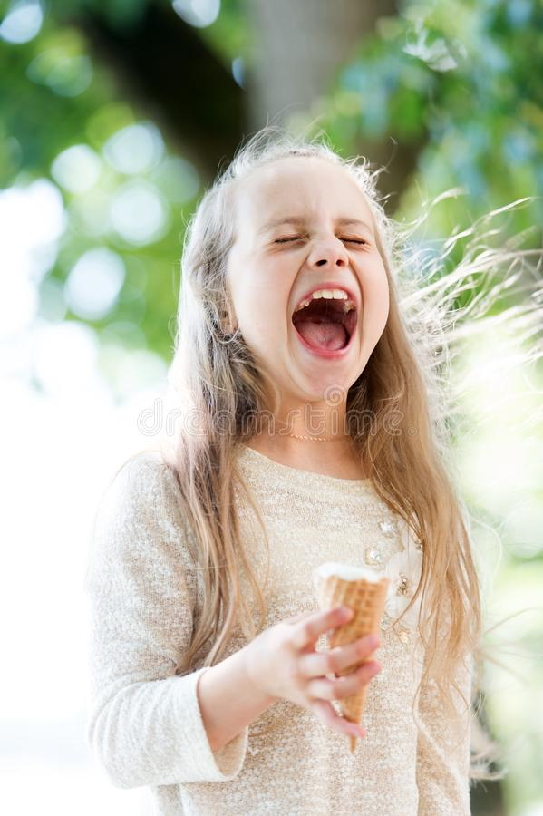 Ice cream makes her fall into euphoria. Cute little girl eating ice cream on summer day. Small child licking ice cream stock photo