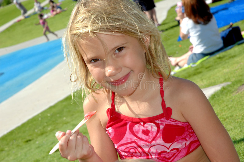 Ice Cream Outside. Young girl eats ice cream at a park in her bathing suit royalty free stock image