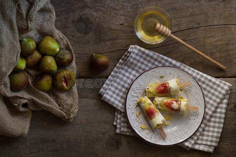 Ice cream pops made with fresh figs on a rustic wooden table. Summer lifestyle. Homemade healthy dessert. Flat lay royalty free stock images