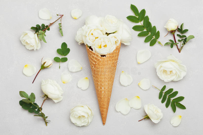 Ice cream of rose flowers in waffle cone on light gray background from above, beautiful floral decoration, vintage color, flat lay royalty free stock images