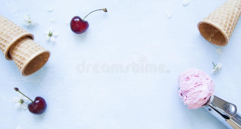 Ice cream scoop, sugar cones, fresh cherries and flowers on optimistic blue background royalty free stock images