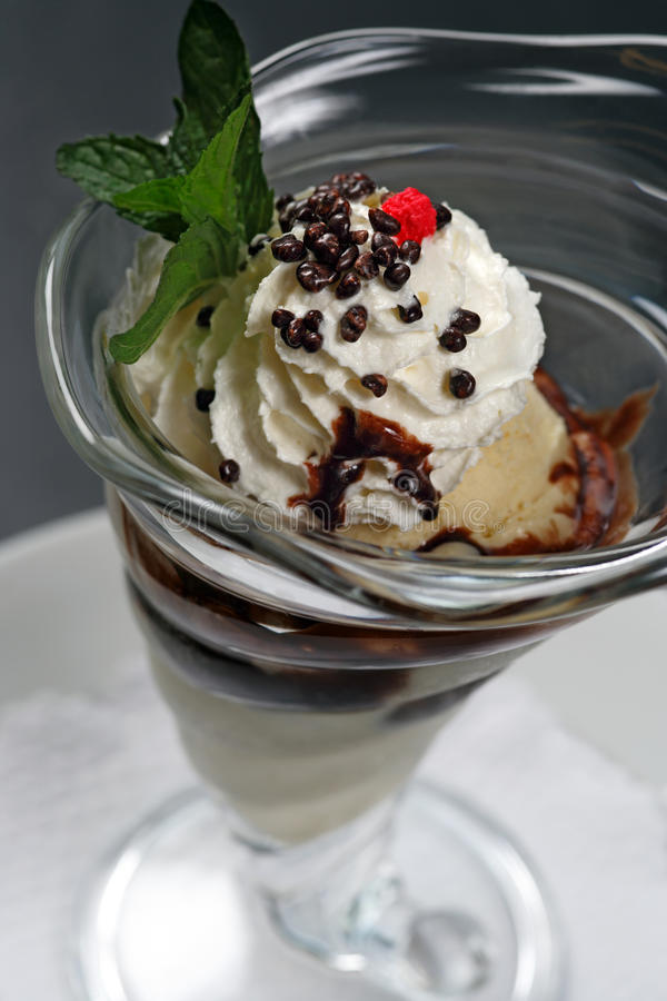 Ice cream sundae. A closeup image of a vanilla ice cream sundae with whipped cream, chocolate covered nuts, chocolate sauce, and a raspberry on top stock photo