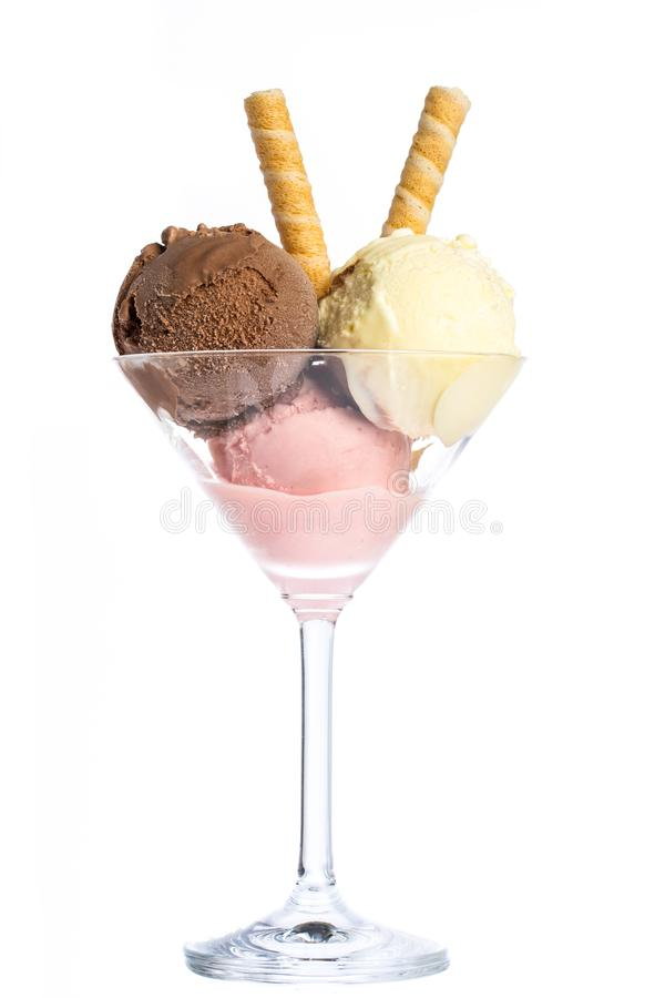 Ice cream: Three scoops of ice cream in red, yellow and brown in a martini glass royalty free stock photos