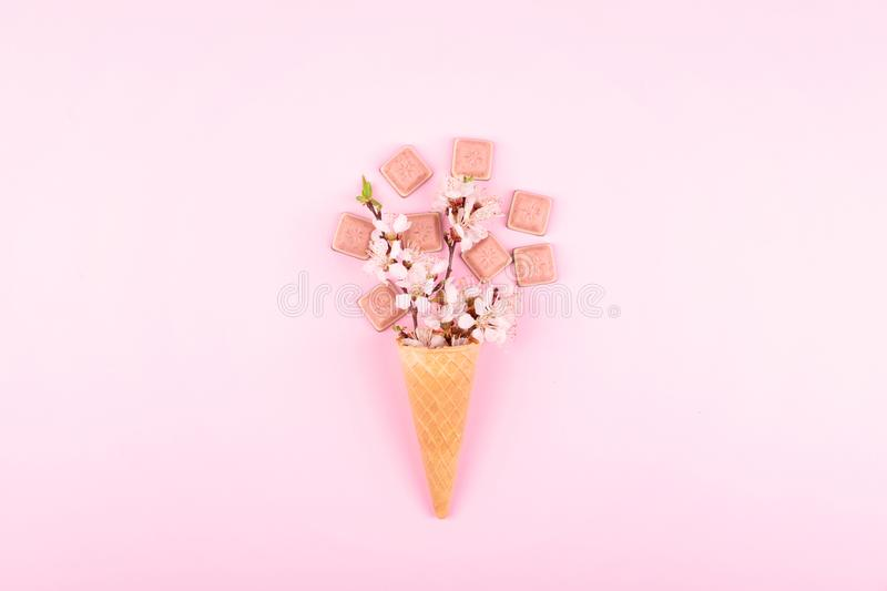 Ice cream waffle cone with colorful flowers and pink chocolate on pink background. Flat lay. Minimal gift birthday concept. Sweet, female, art, summer, spring royalty free stock photos