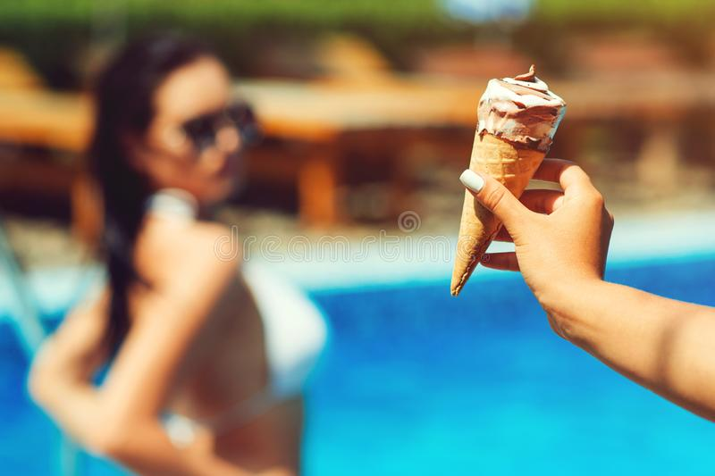 Ice cream on water pool background. Woman`s hand holding a cone of colored ice cream. Girls pool party. Hot summer day. Melting royalty free stock photos