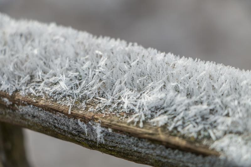 Ice crystals on an old wooden crossbar royalty free stock image
