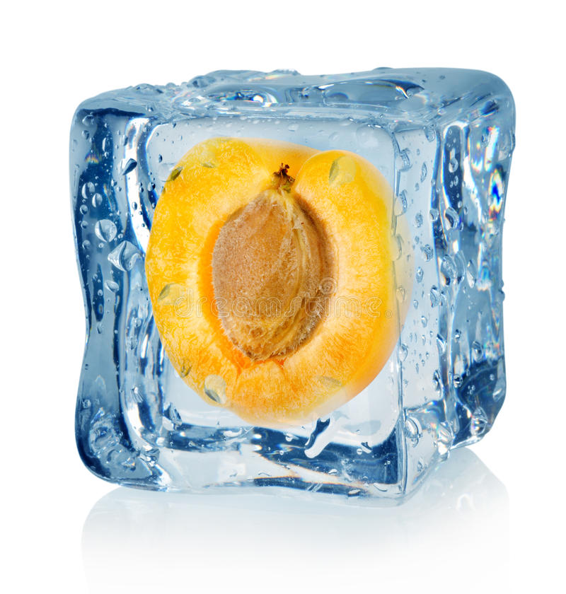 Ice cube and apricot. On a white background royalty free stock photos