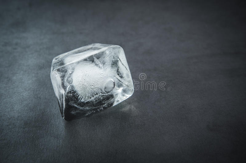 Ice cube. Ice cube on a dark background. Selective focus royalty free stock photo