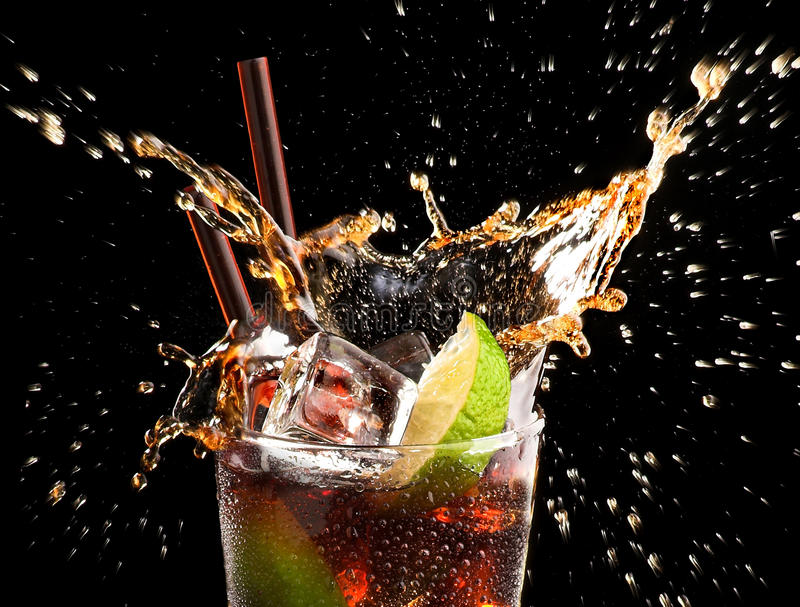 Ice cube and lime droped in cola glass royalty free stock photography