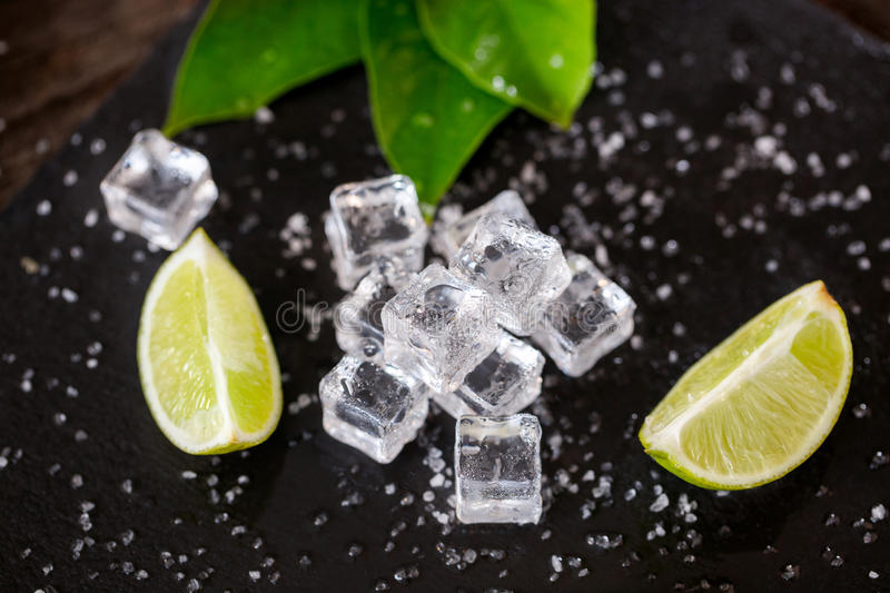 Ice cube with lime slices and salt on dark table royalty free stock image