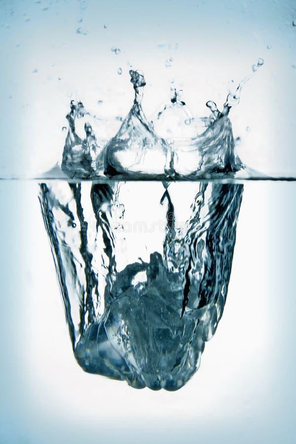 Ice Cube Splashing Into Water. Royalty Free Stock Photo