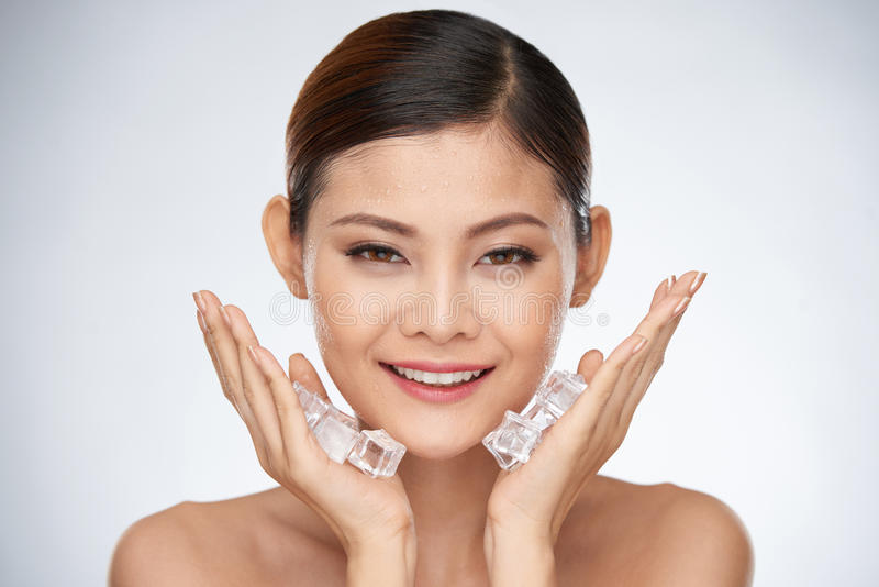 Ice cube treatment. Smiling woman applying ice cube treatment on face stock photography