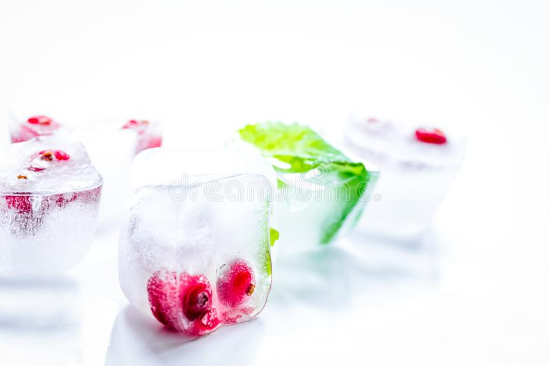 Ice cubes with berries and mint for summer drink on white backgr. Ice cubes with fresh berries and mint for summer drink on white table background stock photos