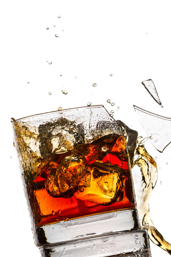 Ice cubes breaking whisky glass. Filled with bourbon on white background royalty free stock image