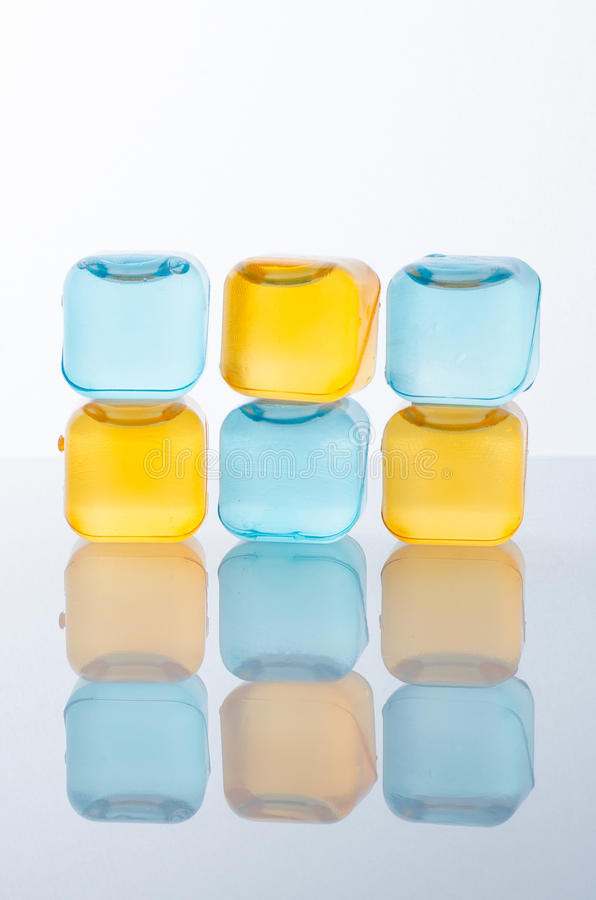 Ice cubes in colored. With reflection on white royalty free stock photos