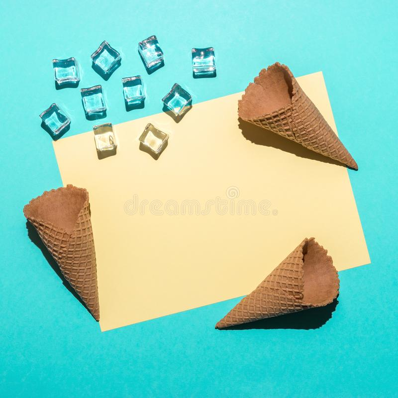 Ice cubes and ice cream cones on bright blue background. Minimal summer composition. Flat lay royalty free stock images