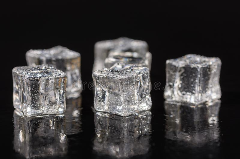 Ice cubes with drops of water on the black background with reflections royalty free stock images
