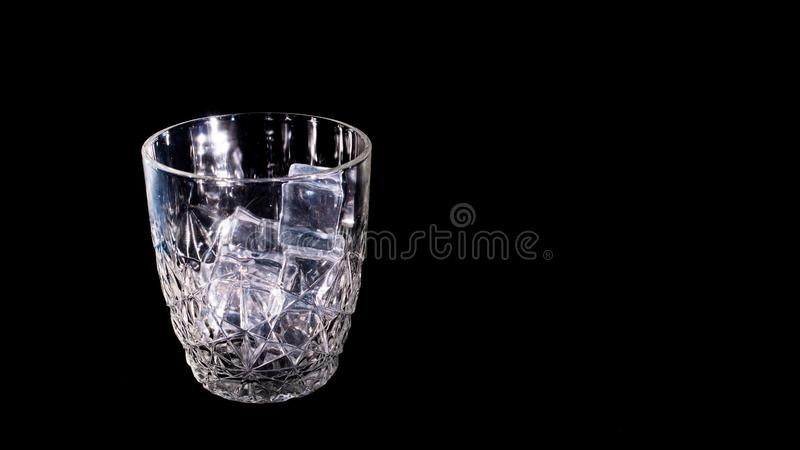 Ice cubes fall into a glass stock photo