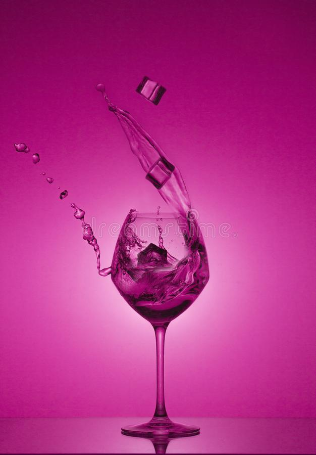 Ice cubes fall into a glass and water is poured out. Water splashing out of a tall wine glass. royalty free stock image