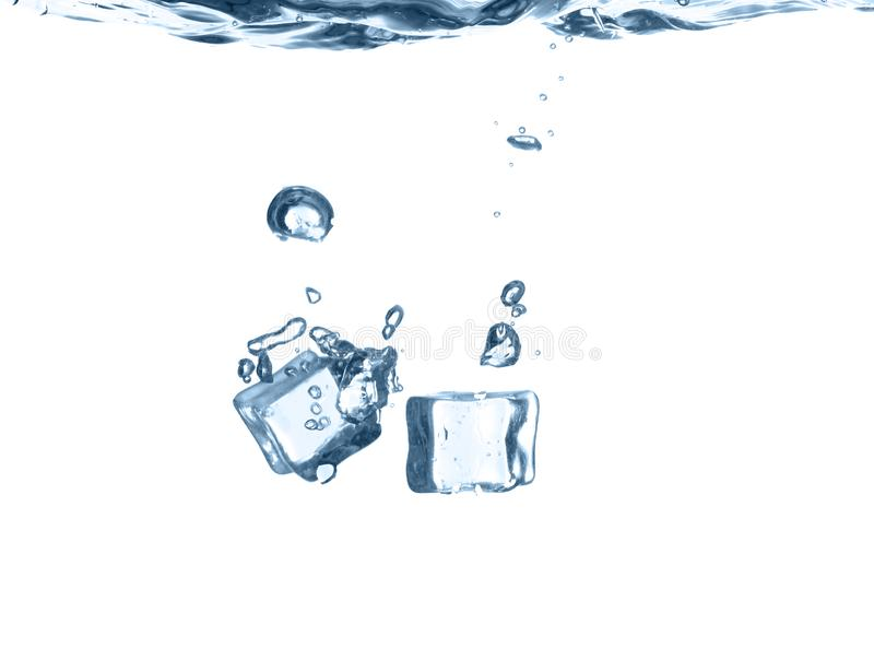 Ice cubes falling into water. Against white background royalty free stock image