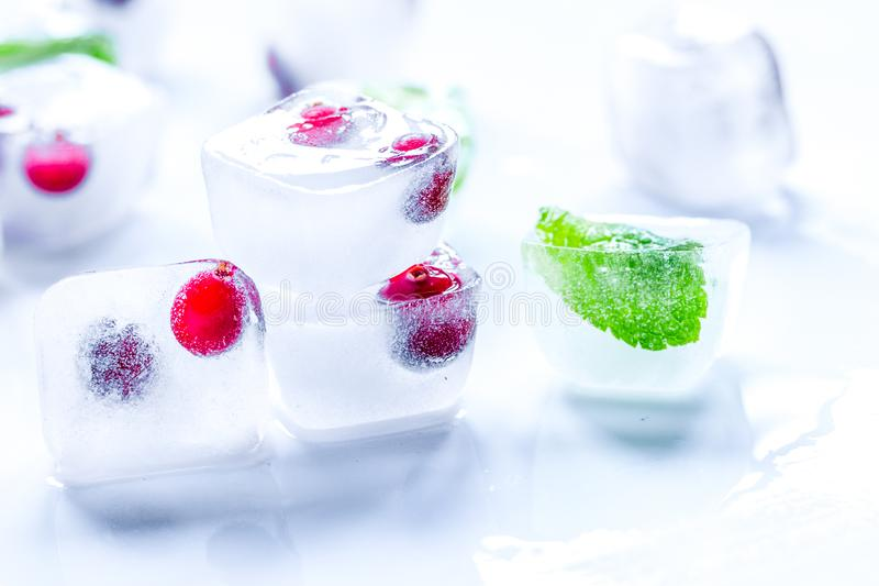 Ice cubes with red berries and mint white background stock photos