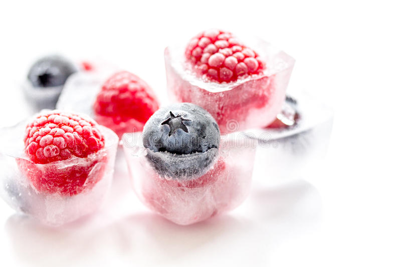 Ice cubes with frozen berries on white background stock photo