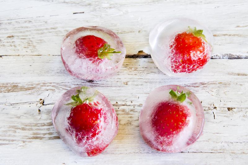 Ice cubes with strawberries stock photography