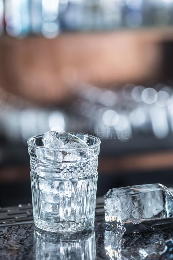 Ice cubes in glass at barcounter in night club or restaurant royalty free stock images