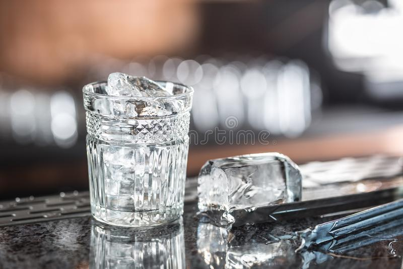 Ice cubes in glass at barcounter in night club or restaurant stock photo