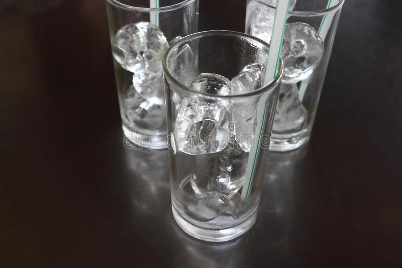 Ice cubes in glass with straw on the table. royalty free stock photos