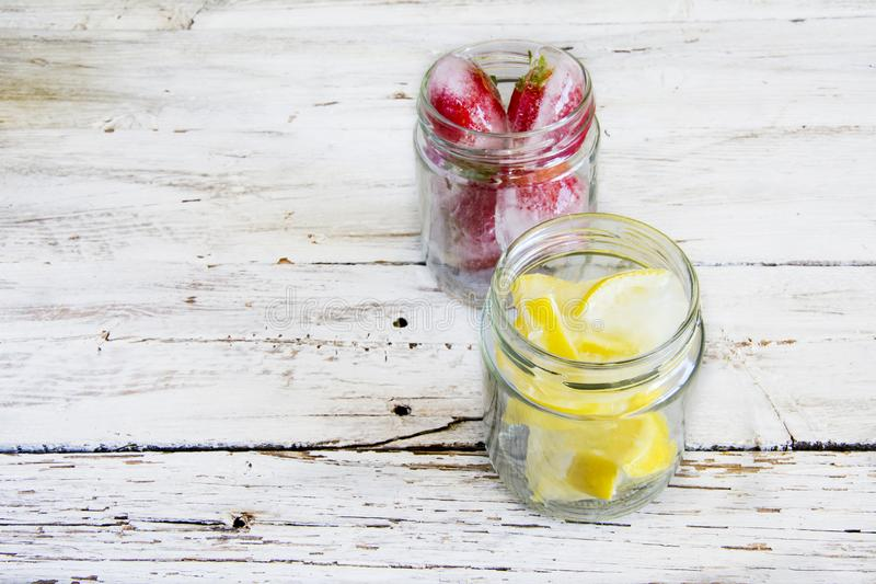 Ice cubes with lemons and strawberries royalty free stock photography