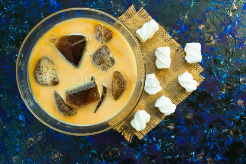 Ice cubes made from coffee with milk on a blue background. Iced coffee and march melo . Cooling drink. Top view. Ice cubes made from coffee with milk on a blue stock photography
