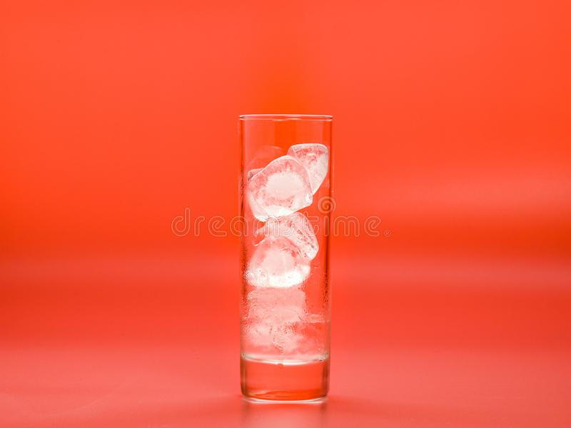 Ice cubes melting down in glass on pink background, close up view. Solid water in glass. Condensate on surface of glass. Selective soft focus. Blurred royalty free stock image