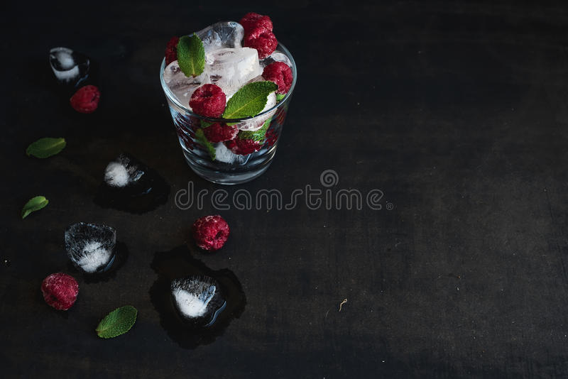 Ice cubes with mint leaves and raspberry in glass on dark grunge surface. Ice cubes with mint leaves and raspberry in glass on dark grunge background with copy royalty free stock images