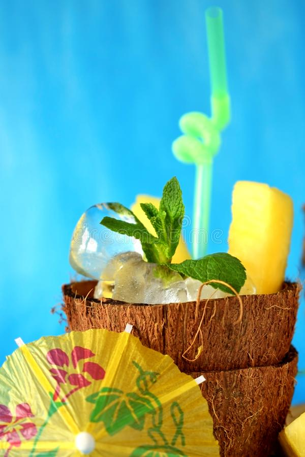 Ice cubes and pineapple pieces served in a coconut half royalty free stock photography