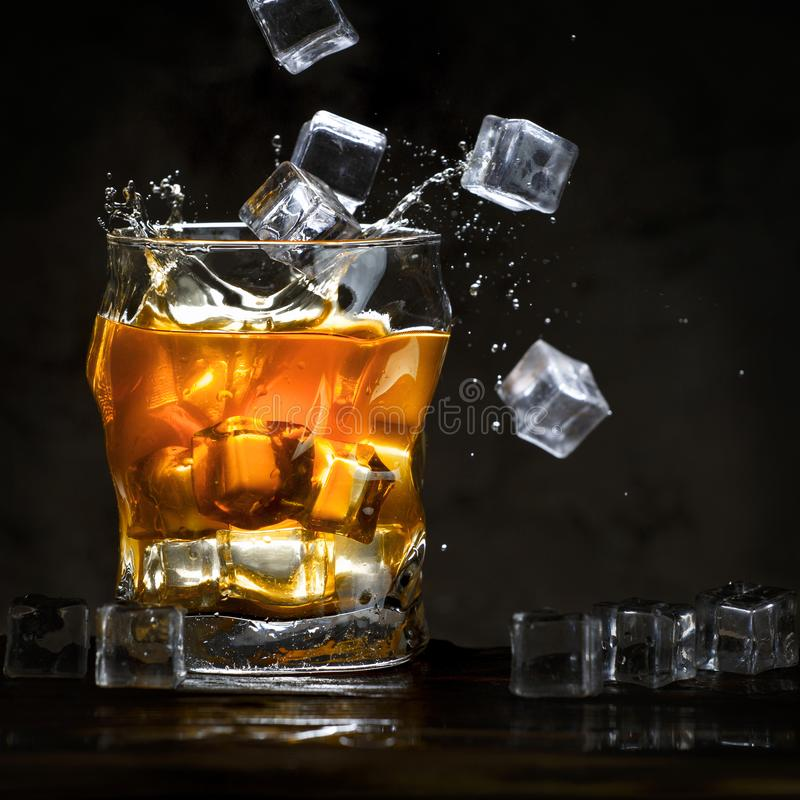 Ice cubes pour into a glass with alcohol. stock photo