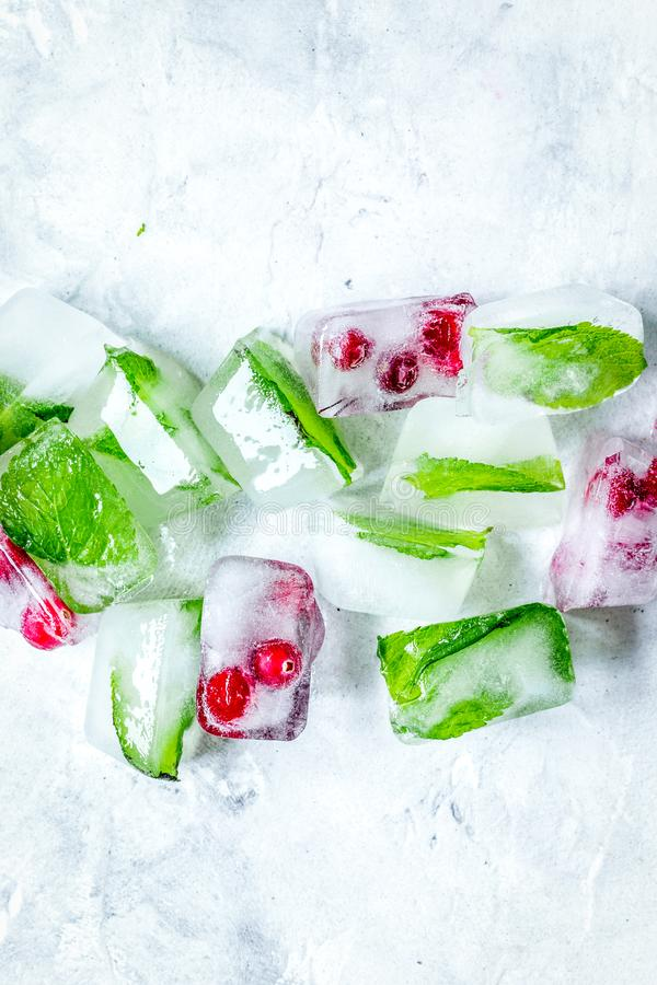 Ice cubes with red berries and mint top view gray stone background mockup stock photos