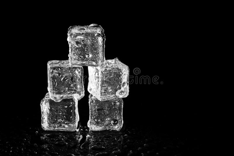 Ice cubes reflection on black table background. Abstract, bar, beautiful, block, blocks, bright, clean, clear, closeup, cold, cool, cracked, crushed, crystal stock images