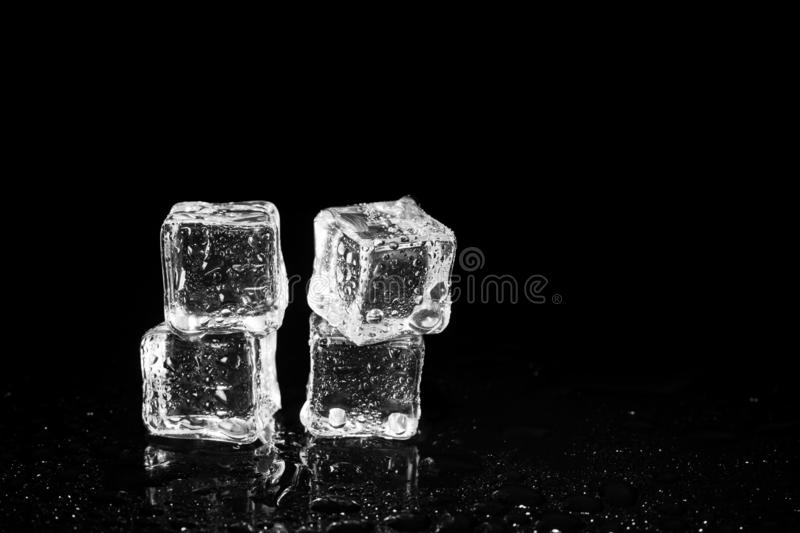 Ice cubes reflection on black table background. Abstract, bar, beautiful, block, blocks, bright, clean, clear, closeup, cold, cool, cracked, crushed, crystal royalty free stock photo