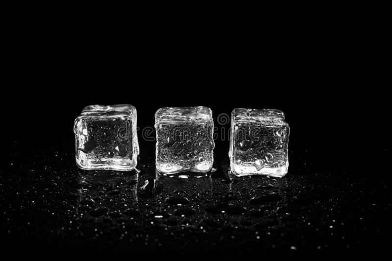 Ice cubes reflection on black table background. Abstract, bar, beautiful, block, blocks, bright, clean, clear, closeup, cold, cool, cracked, crushed, crystal royalty free stock images