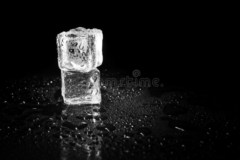 Ice cubes reflection on black table background. Abstract, bar, beautiful, block, blocks, bright, clean, clear, closeup, cold, cool, cracked, crushed, crystal stock image